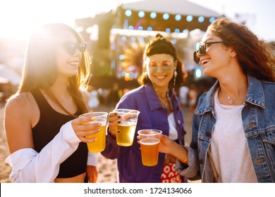 Young girlfriends drinking beer and having fun at music festival. Friendship and celebration. Beach party, summer holiday, vacation concept.