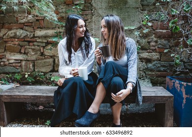 Young girlfriends talk about drinking coffee during break from work