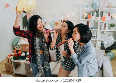 young girls best friends celebrating graduation party in house. female students playing with whistles and balloons having fun at decorated home. enjoyment friendship never end concept.
