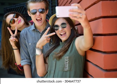 Young girls and boy having fun outdoor and making selfie with smart phone against red brick wall. Urban lifestyle, happiness, joy, friends, social network concept. Image toned and noise added.