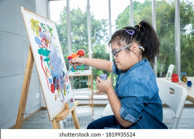 Young girls disabilities Or Down Syndroms learning about painting watercolor and bright smile for active learning and encouraging beside. Education and special child  concept.
