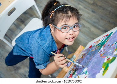 Young girls disabilities Or Down's syndrome learning about painting watercolor and bright smile for active learning and encouraging beside. Education and special child  concept.