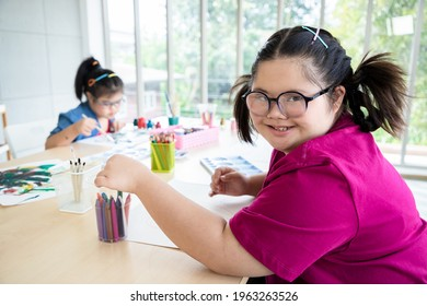 Young girls disabilities Or Down's syndrome learning art and painting with bright smile for active learning and encouraging beside. Education and special child concept.