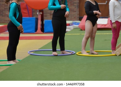 Young girls doing gymnastics with hula hoops