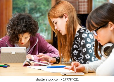 Young girls doing homework together at desk with tablets.