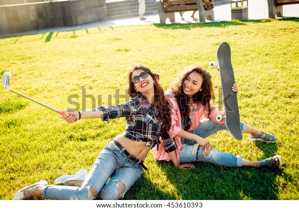 Young girls doing selfie with a skateboard. In the park