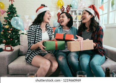 young girls enjoy chilling at home celebrating xmas. three of best friends exchanging presents on christmas house party laughing having fun sitting on couch. asian teenagers with gifts and santa hats