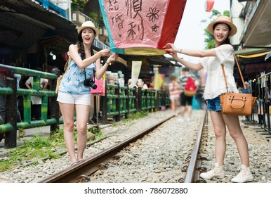 "young girls enjoy taiwan travel write their wishes on the sky lanterns ready to let go. Translation on sky lanterns text ""hopes of happiness and good luck in love life in the future""."