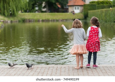 Young girls feeding birds by the city pond. Throwing bread to ducks. Pretty colorful dresses and skirts, long hair.