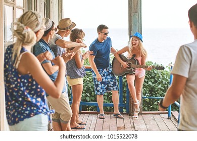 Young girl's first funny attempt at playing the guitar in company of friends while hanging out on vacation at an old wooden cabin porch by the sea.