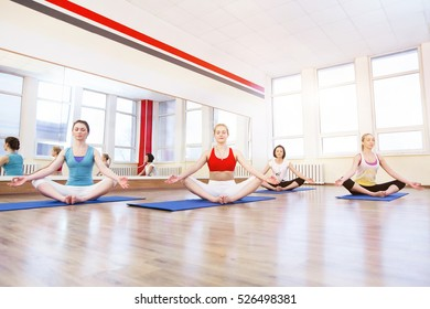 Young girls and fitness, sport, training, yoga. Group yoga concept - smiling woman doing exercise in gym. Yoga team in gym class in lotus posture