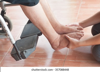 Young girl's foot touches and holds an old woman's wrinkled foot.