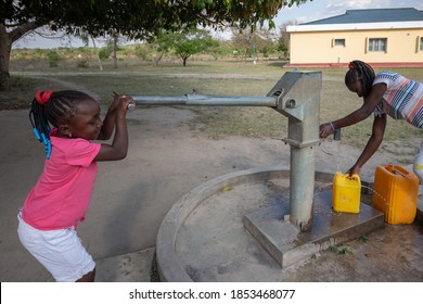 Young girls getting fresh water in the community hand water pump in rural Africa