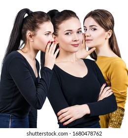 Young girls gossiping some secret. Over white background.