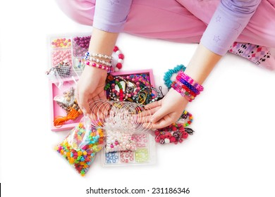 Young Girl's Hand with Many Different Beads and Jewelry. Isolated on White Background.