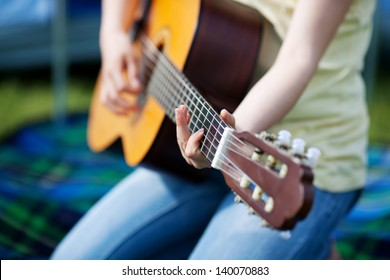 Young girls hands playing guitar against tent