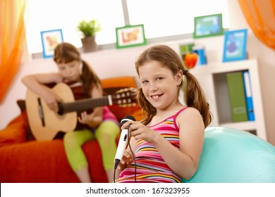 Young girls having fun with music at home, playing guitar, singing with microphone.