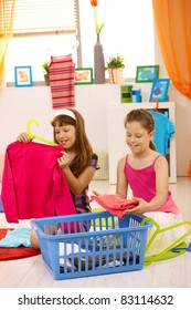 Young girls helping at home, packing clothes, smiling.?