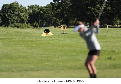 a young girls hits golf balls on a driving range