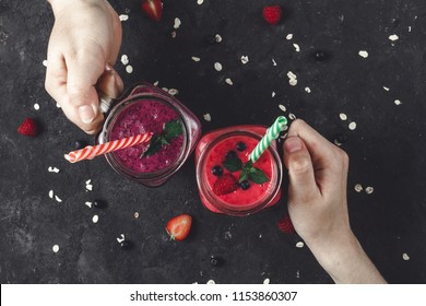 Young girls are holding fresh, cold, sweet smoothies from raspberries and blueberries with fresh berries and a piece of mint. Healthy diet. Summer. Top view