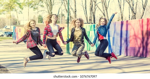 Young girls holding hands and jumping together