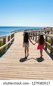 Young girls holding hands walking on the boardwalk in Bouctouche along the Atlantic Ocean, New Brunswick, in the Maritimes, Eastern Canada