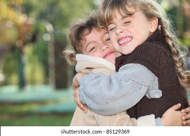 Young girls hugging outside
