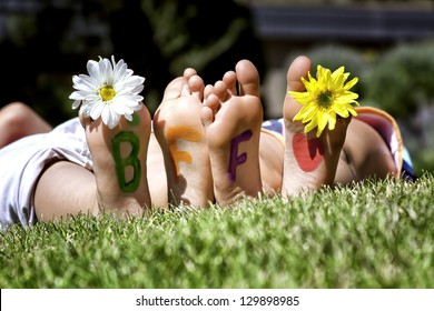Young girls laying in the grass with daisies in their toes and best friends forever painted on the bottoms of their feet