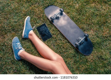 Young girls legs, tablet computer and skateboard lying near each other on grass top view