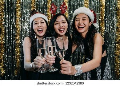 young girls on christmas eve party with red reindeer cheers. asian ladies cheerfully clinking wine glasses celebrating single party before marriage. group of best friends wearing modern sexy dresses.
