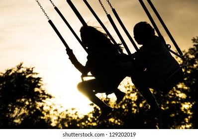 Young girls on Merry Go Round at Sunset