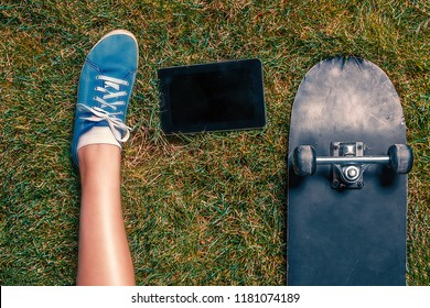 young Girls one leg in teal canvas trainer, tablet computer and skateboard on grass top view