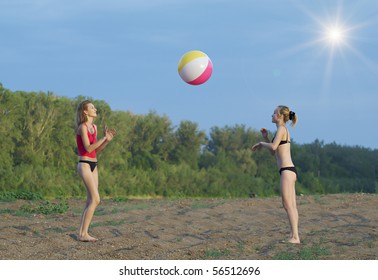 Young girls playing with a ball on the sandy beach