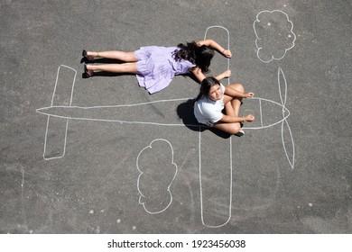 Junge Mädchen, die mit einem Kreideflugzeug im Park spielen