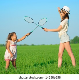 The young girls plays with a racket in badminton over green grass