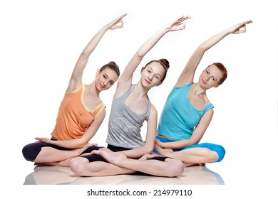 young girls practicing yoga on white background, meditating in lotus position.