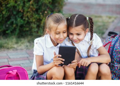 Young girls reading an tablet. Pupils of primary school. Girls with backpacks near building outdoors
