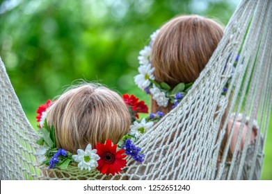 young girls resting in hammock during Swedish midsummer celebrations with flowers in their hair.