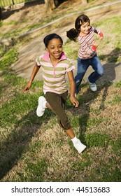 Young girls running on grass. Vertically framed shot.