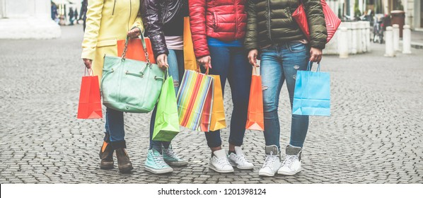 Young girls with shopping bags in city downtown center - Girls going around shops for the sales time - Buyers female addiction, fashion clothes and consumerism concept