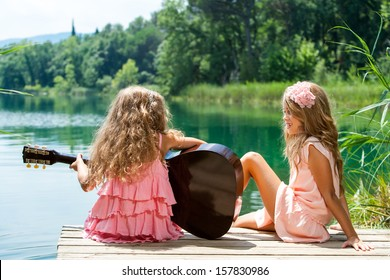 Young girls singing together with spanish guitar at lake.
