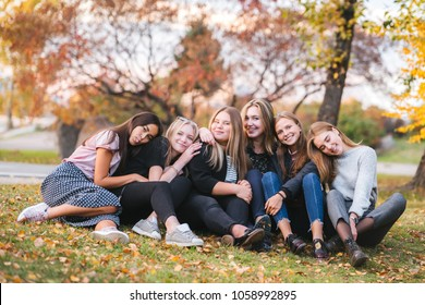 Young girls sit on the grass in the Park. Group of girlfriends laughing