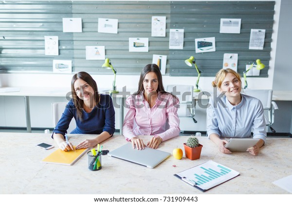 Young girls are sitting at the office at the table.
