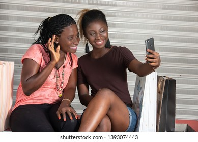 young girls sitting outside looking at mobile phone while smiling.