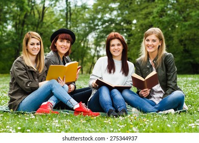 Young girls sitting in the park and learning.Students