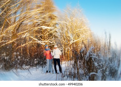 Young girls skiing in winter forest