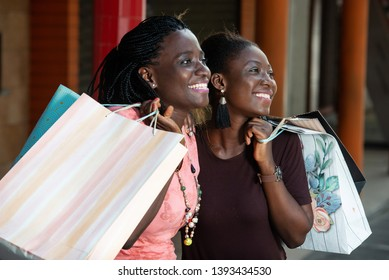 young girls standing in a mall with shopping bags and look at goods smiling.