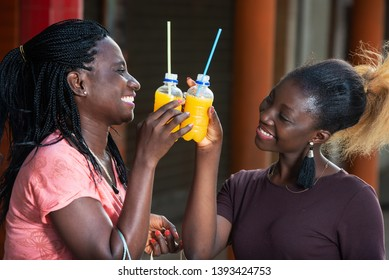 young girls standing outside banging bottles of fruit juice together laughing.