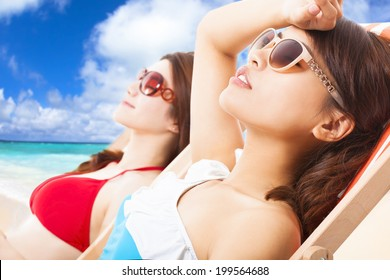young girls sunbathing and lying on a beach chair