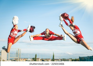 Young girls teenager cheerleaders team performing a jump with male coach - American style culture - High school college sports